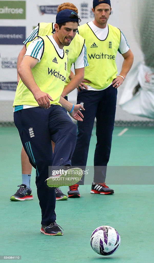 England's captain Alastair Cook (L) kicks a football as he warms-up with teammates during an indoor practice session ahead of the second cricket Test match between England and Sri Lanka in Chester-le-Street, north east England on May 26, 2016. England may come into the second Test against Sri Lanka in Durham on the back of a crushing win in the series opener, but according to Stuart Broad the hosts have still to hit top form. England are set to play Sri Lanka in a second test cricket match on May 27. / AFP / SCOTT