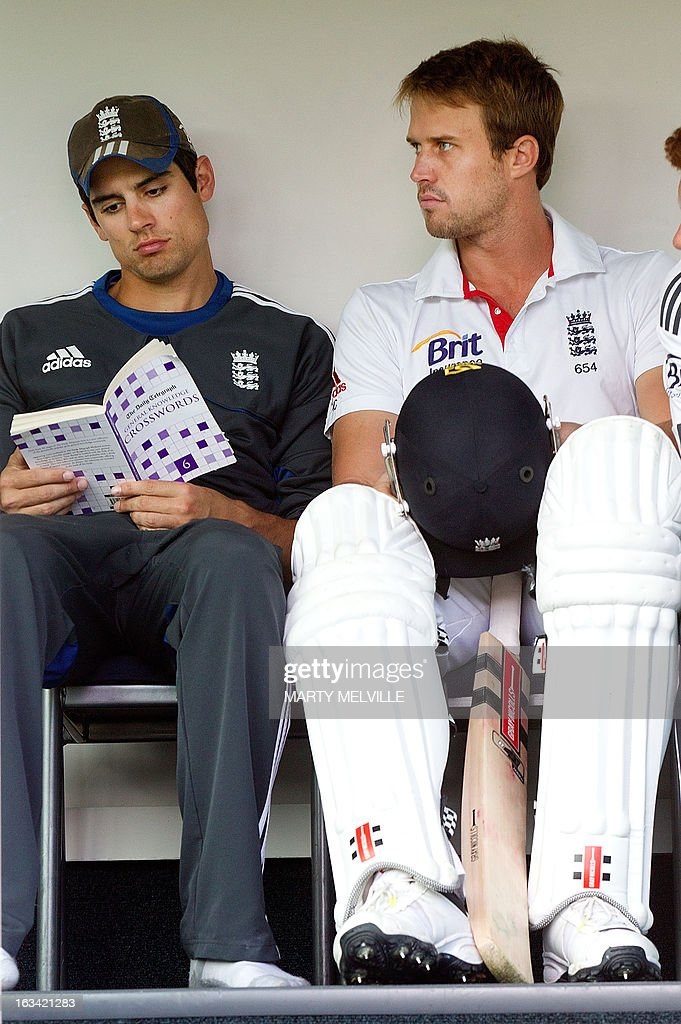 England's captain Alastair Cook (L) kills time with a crossword book as team mate Nick Compton waits to bat at the start of the days play during day four of the first international cricket test match between New Zealand and England played at the University Oval park in Dunedin on March 9, 2013. AFP PHOTO / Marty MELVILLE