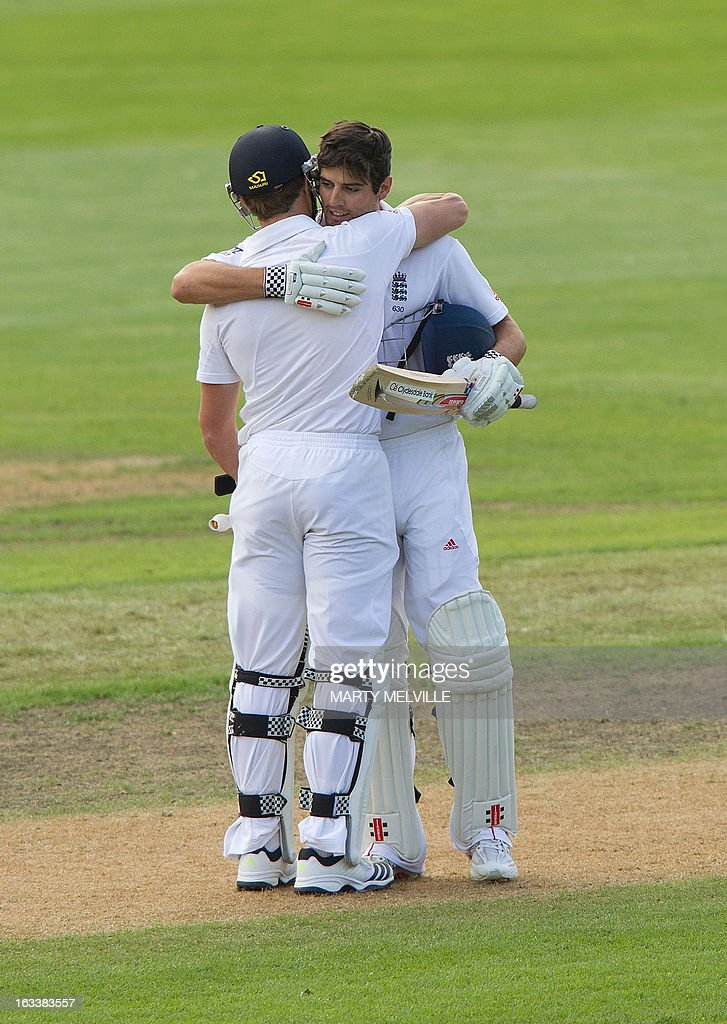 England's captain Alastair Cook (R is hugged by teammate Nick Compton after he scored 100 runs during day four of the first international cricket Test match between New Zealand and England played at the University Oval park in Dunedin on March 9, 2013. AFP PHOTO / Marty MELVILLE