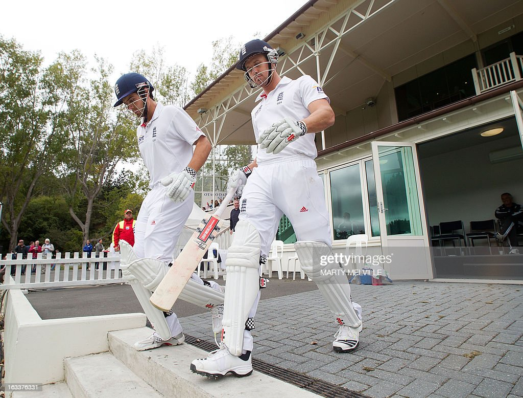 England's captain Alastair Cook (L) with team mate Nick Compton walk out to the field at start of play after lunch during day four of the first international cricket Test match between New Zealand and England played at the University Oval park in Dunedin on March 9, 2013. AFP PHOTO / Marty MELVILLE
