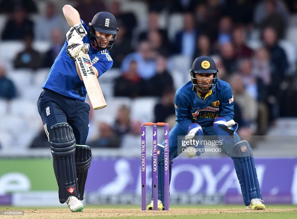 England's captain Eoin Morgan plays a shot watches by Sri Lanka's Dinesh Chandimal (R) during play in the fourth One Day International (ODI) cricket match between England and Sri Lanka at The Oval cricket ground in London on June 29, 2016. England's victory target was revised to 308 off 42 overs due to the weather having seen the tourists show real guile and style in their innings. / AFP / OLLY