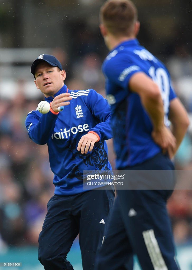 England's captain Eoin Morgan (L) throws the ball to teammate England's Chris Woakes during the fourth One Day International (ODI) cricket match between England and Sri Lanka at The Oval cricket ground in London on June 29, 2016. / AFP / OLLY