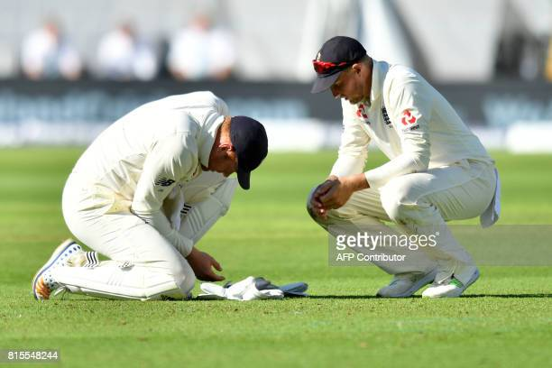 England's captain Joe Root signals for medical assistance for England's Jonny Bairstow who injured his hand whilst fielding on the third day of the...