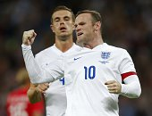 England's captain Wayne Rooney celebrates scoring the opening goal from the penalty spot during the international friendly football match between...