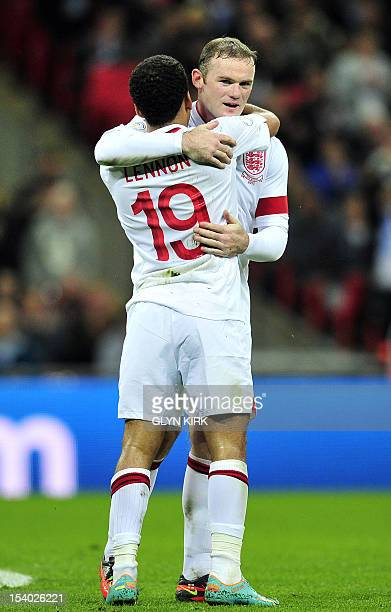 England's captain Wayne Rooney celebrates scoring their fourth goal with Aaron Lennon during the 2014 World Cup qualifying football match between...
