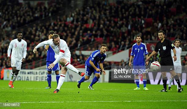 England's captain Wayne Rooney scores the opening goal from a penalty spot during the 2014 World Cup qualifying football match between England and...