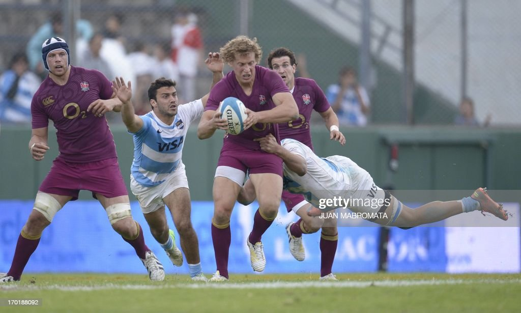 England's centre Billy Twelvetrees (C) is tackled by Argentina's Los Pumas flanker Benjamin Macome (R) and scrum half Martin Landajo during their rugby union international test match at Padre Ernesto Martearena stadium in Salta, on June 8, 2013. England won 32-3. AFP PHOTO / Juan Mabromata