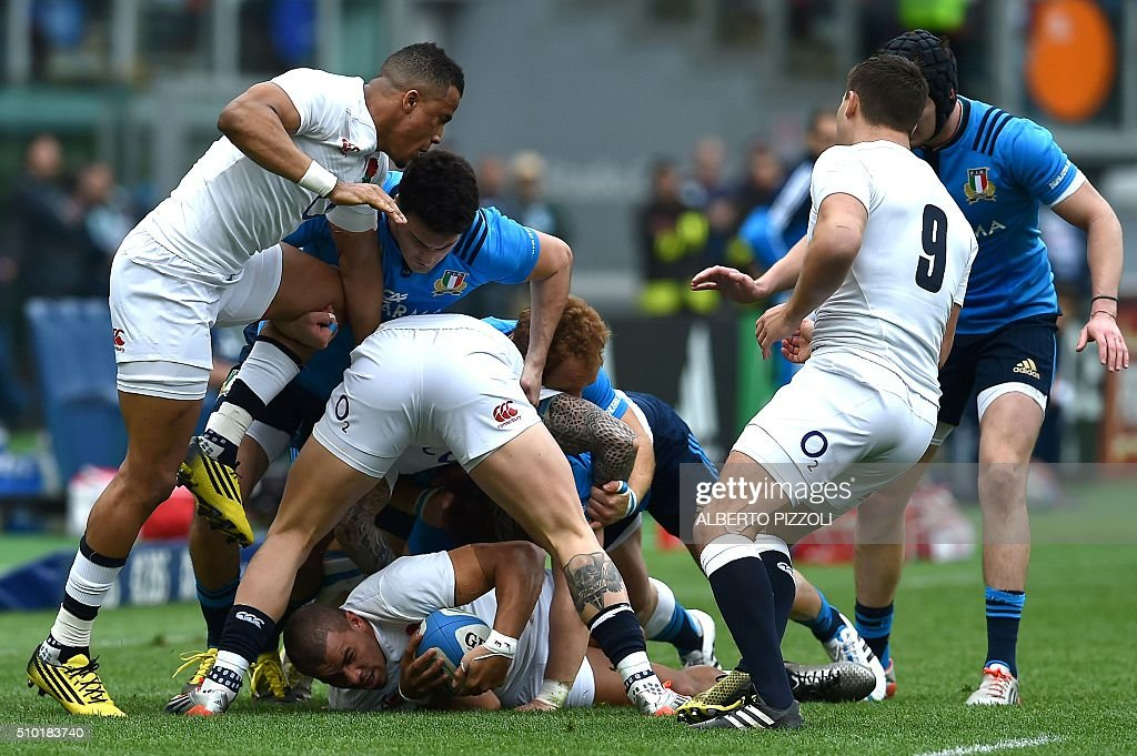 England's centre Jonathan Joseph (under) is takled during the Six Nations international rugby union match between Italy and England on February 14, 2016 at Olympic stadium in Rome. / AFP / ALBERTO PIZZOLI
