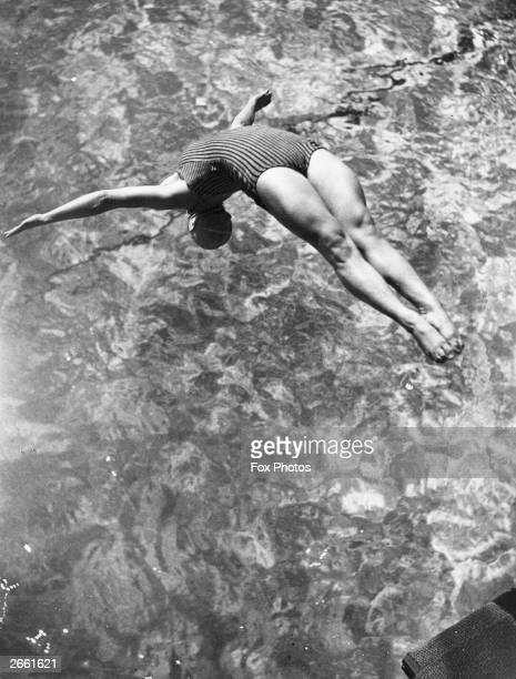 England's champion woman diver Betty Slade doing a back dive from the springboard during training at Wood Green baths