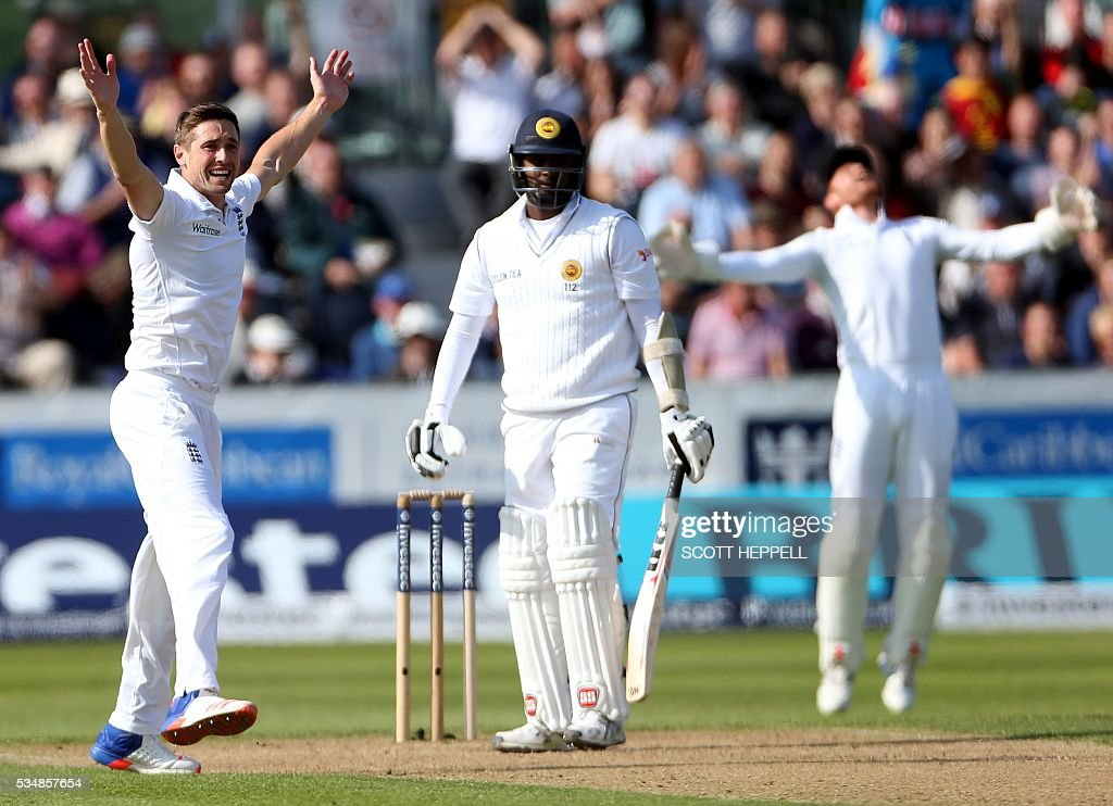 England's Chris Woakes (L) celebrates after taking the wicket of Sri Lanka's Angelo Mathews (C) off a catch by England's wicket keeper Jonny Bairstow (R) for 3 runs on the second day of the second test cricket match between England and Sri Lanka at the Riverside in Chester-Le-Street, north east England on May 28, 2016. / AFP / SCOTT