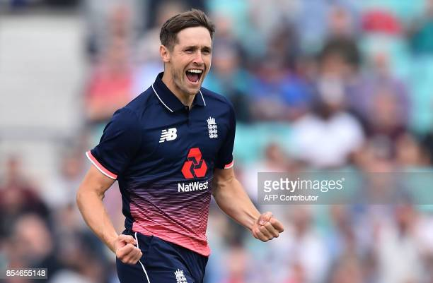 England's Chris Woakes celebrates the wicket of West Indies' Chris Gayle for two during the fourth OneDay International cricket match between England...