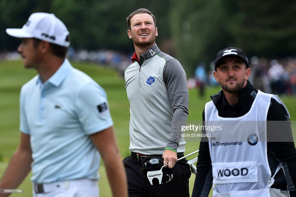 England's Chris Wood (C) reacts after putting out on the 18th hole during the fourth day of the golf PGA Championship at Wentworth Golf Club in Surrey, south west of London, on May 29, 2016. / AFP / BEN