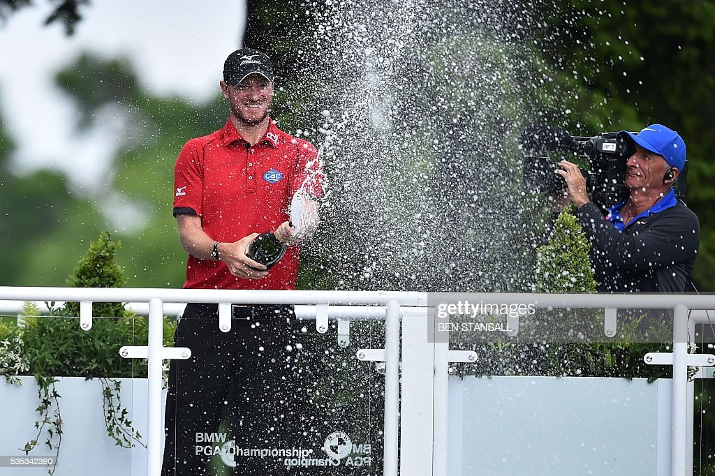 England's Chris Wood sprays champagne as he celebrates after winning the golf PGA Championship at Wentworth Golf Club in Surrey, south west of London, on May 29, 2016. / AFP / BEN