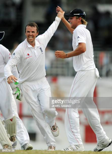 England's cricketer Graeme Swann celebrates with his teammate Stuart Broad after dismissing West Indies cricketer Daren Powell during the third day...