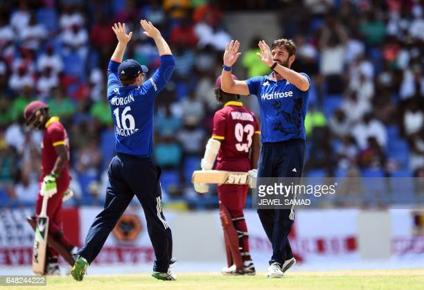 England's cricketer Liam Plunkett celebrates with team captain Eoin Morgan after dismissing West Indies batsman Jason Mohammed during the second of...