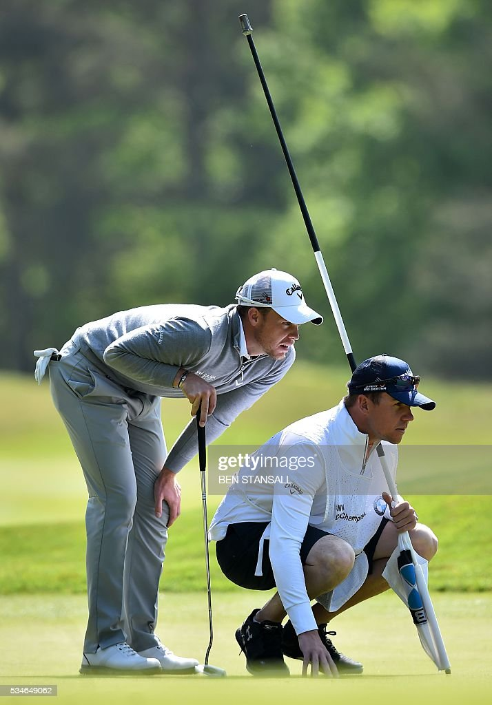 England's Danny Willett (L) and his caddie Jonathan Smart (R) line up his put on the 9th green on the second day of the PGA Championship at Wentworth Golf Club in Surrey, south west of London on May 27, 2016. / AFP / BEN