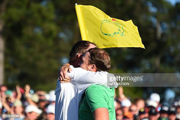 England's Danny Willett embraces his caddie Jonathan Smart after putting on the 18th green during Round 4 of the 80th Masters Golf Tournament at the...