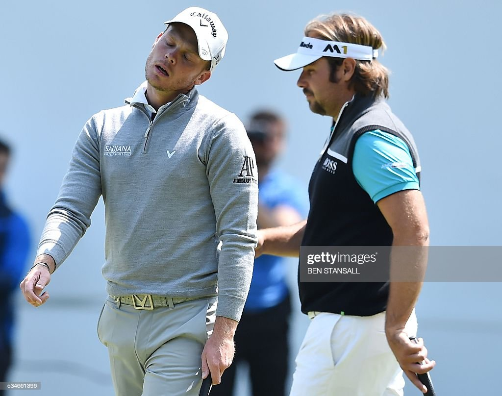 England's Danny Willett (L) reacts after missing a putt on the 18th hole as France's Victor Dubuisson (R) looks on during the second day of the PGA Championship at Wentworth Golf Club in Surrey, south west of London, on May 27, 2016. / AFP / BEN