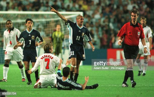 England's David Beckham protests his innocence before being shown the red card by referee Kim Milton Neilsen for kicking Diego Simeone of Argentina