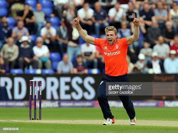 England's David Willey celebrates taking the wicket of Australia's David Warner during the Twenty20 International cricket match between England and...