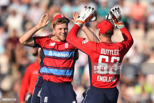 England's David Willey celebrates with England's Jos Buttler after bowling South Africa's JJ Smuts with the first ball of the T20 international...