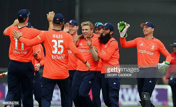 England's David Willey celebrates with teammates after taking the wicket of Australia's David Warner during the Twenty20 International cricket match...
