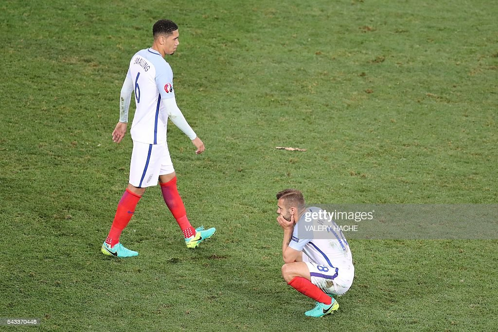 England's defender Chris Smalling (L) and England's midfielder Jack Wilshere react after the Euro 2016 round of 16 football match between England and Iceland at the Allianz Riviera stadium in Nice on June 27, 2016. Iceland won the match 1-2. / AFP / Valery HACHE