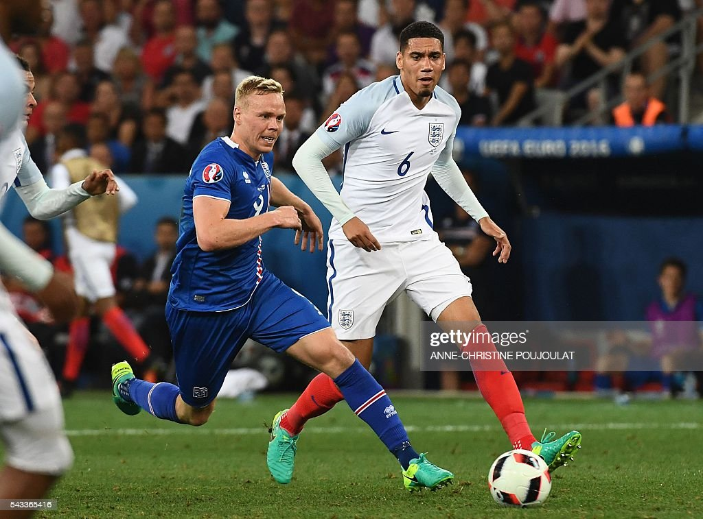 England's defender Chris Smalling (R) and Iceland's forward Kolbeinn Sigthorsson vie for the ball during Euro 2016 round of 16 football match between England and Iceland at the Allianz Riviera stadium in Nice on June 27, 2016. / AFP / ANNE