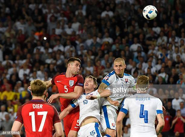 TOPSHOT England's defender Gary Cahill vies for the header with Slovakia's defender Tomas Hubocan and Slovakia's defender Martin Skrtel during the...