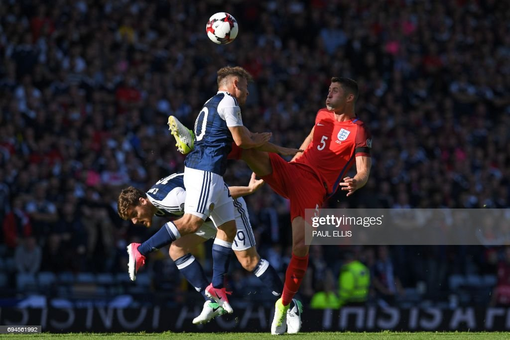 England's defender Gary Cahill (R) vies with Scotland's striker Chris Martin and Scotland's midfielder Ryan Fraser (C) during the group F World Cup qualifying football match between Scotland and England at Hampden Park in Glasgow on June 10, 2017. The game ended 2-2. / AFP PHOTO / Paul ELLIS / NOT