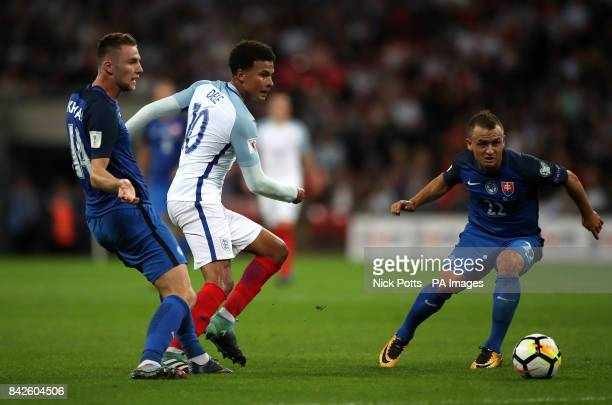 England's Dele Alli battles for the ball with Slovakia's Stanislav Lobotka and Milan Skriniar during the 2018 FIFA World Cup Qualifying Group F match...