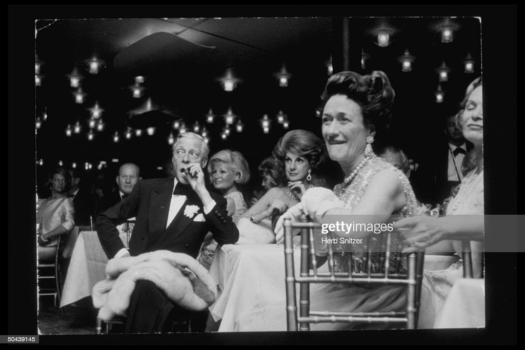 England's Duke of Windsor smoking cigar while sitting at table w. wife Wallis Simpson (R) & unidents.