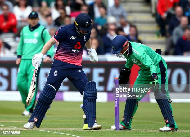 England's Eoin Morgan and Ireland's wicket keeper Niall O'Brien both keep their eye on the ball as it rolls back and rests against the stumps during...