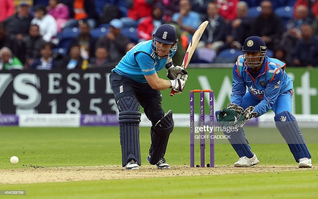 England's Eoin Morgan (L) plays a shot as India's wicket keeper Mahendra Singh Dhoni (R) looks on during the second one-day international cricket match between England and India at the Glamorgan County Cricket Ground in Cardiff, Wales on August 27, 2014. India won by 133 runs.