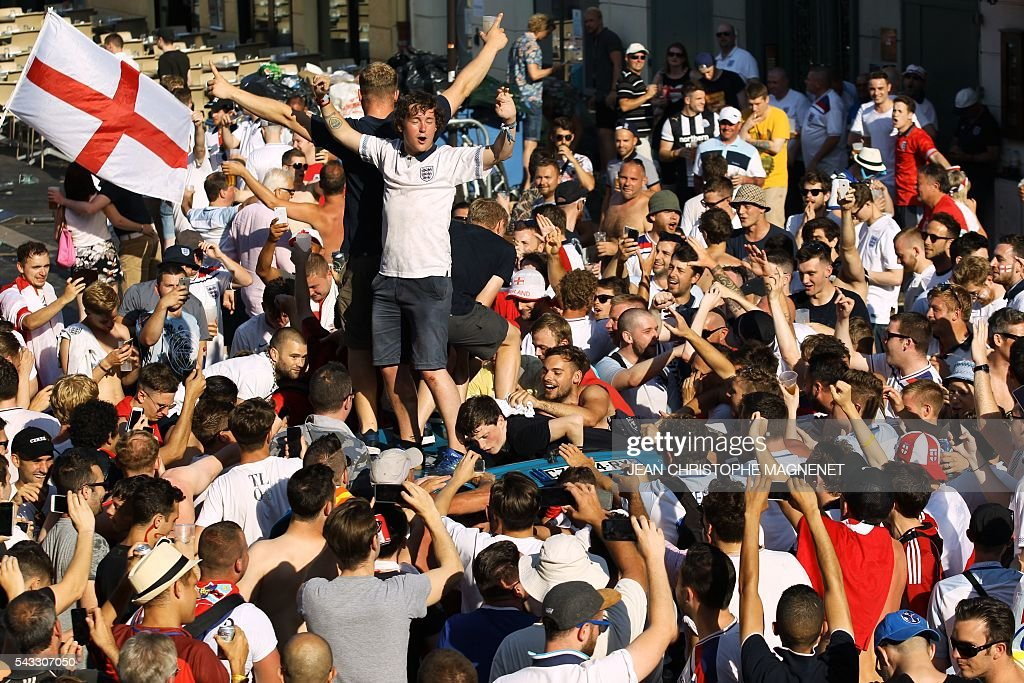 England's fans stand on a car roof as they gather ahead of the Euro 2016 football tournament match England vs Iceland on June 27, 2016 in Nice, southeastern France. / AFP / JEAN