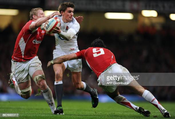 England's flyhalf Toby Flood is tackled by Wales' lock Bradley Davies and scrumhalf Mike Phillips during the Six Nations International rugby union...