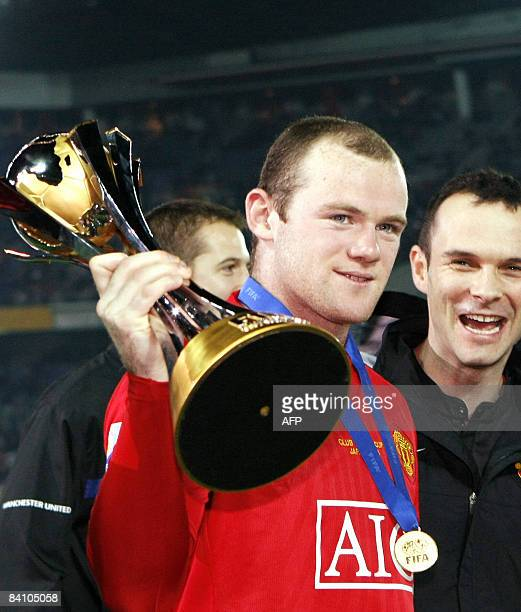 England's football club Manchester United forward Wayne Rooney is all smiles as he hold the trophy of the FIFA Club World Cup 2008 against Ecuador's...