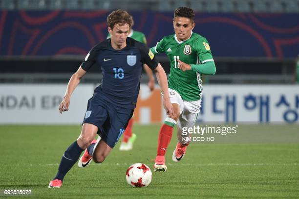 England's forward Dominic Solanke dribbles the ball in front of Mexico's midfielder Kevin Magana during the U20 World Cup quarterfinal football match...