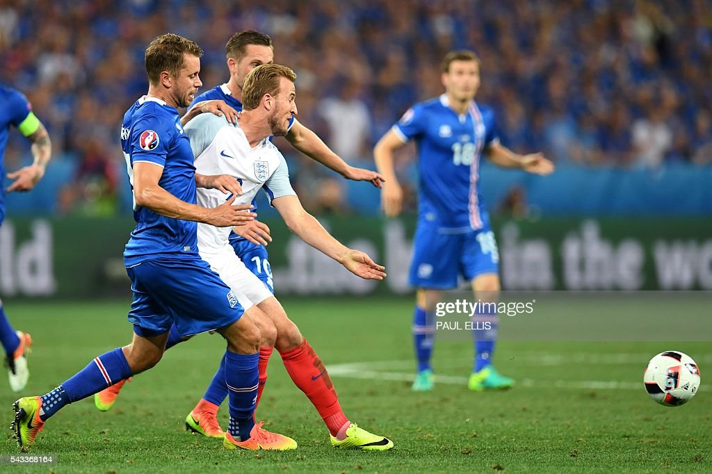 England's forward Harry Kane (C) vies for the ball against Iceland's midfielder Gylfi Sigurdsson (L) and Iceland's defender Kari Arnasonduring Euro 2016 round of 16 football match between England and Iceland at the Allianz Riviera stadium in Nice on June 27, 2016. / AFP / PAUL