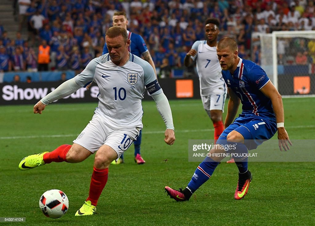 England's forward Wayne Rooney (L) and Iceland's forward Johann Berg Gudmundsson vie for the ball during Euro 2016 round of 16 football match between England and Iceland at the Allianz Riviera stadium in Nice on June 27, 2016. / AFP / ANNE