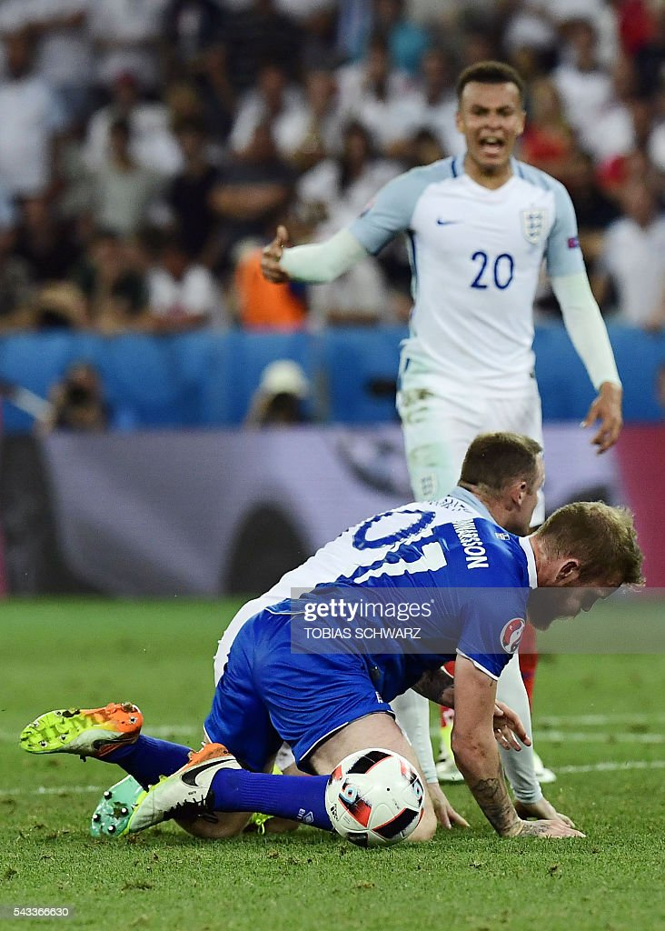 England's forward Wayne Rooney (C) and Iceland's midfielder Aron Gunnarsson (front) kneel on the pitch after vying for the ball during Euro 2016 round of 16 football match between England and Iceland at the Allianz Riviera stadium in Nice on June 27, 2016. / AFP / TOBIAS