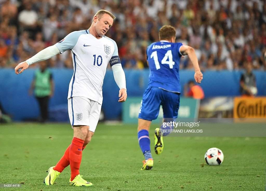 England's forward Wayne Rooney (L) reacts next to Iceland's defender Kari Arnason during the Euro 2016 round of 16 football match between England and Iceland at the Allianz Riviera stadium in Nice on June 27, 2016. / AFP / BERTRAND