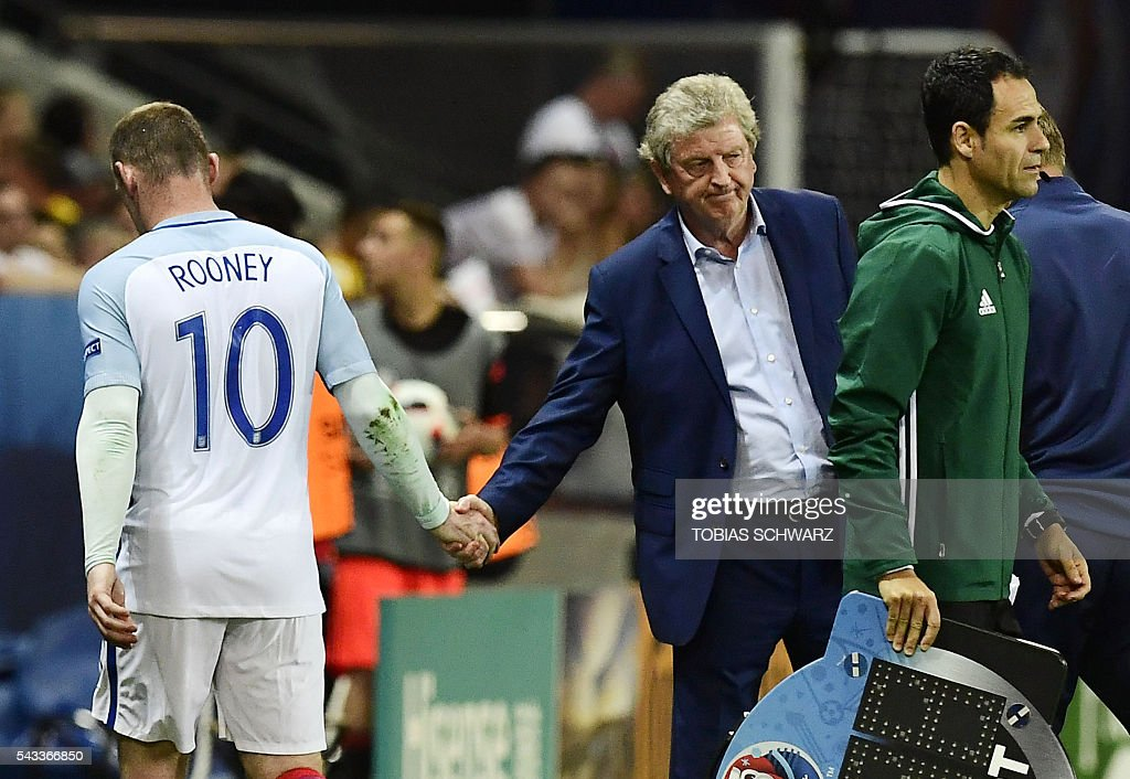 England's forward Wayne Rooney shakes hands with England's coach Roy Hodgson as he is substituted with England's forward Marcus Rashford during Euro 2016 round of 16 football match between England and Iceland at the Allianz Riviera stadium in Nice on June 27, 2016. / AFP / TOBIAS