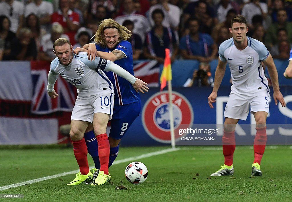 England's forward Wayne Rooney (L) vies for the ball against Iceland's midfielder Birkir Bjarnason as England's defender Gary Cahill (R) looks on during Euro 2016 round of 16 football match between England and Iceland at the Allianz Riviera stadium in Nice on June 27, 2016. / AFP / TOBIAS