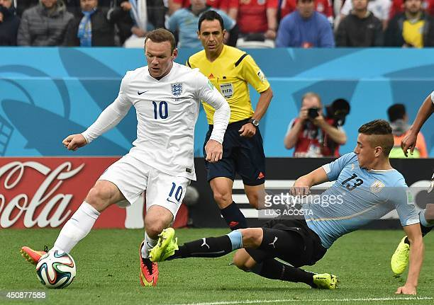 England's forward Wayne Rooney vies with Uruguay's defender Jose Maria Gimenez during a Group D football match between Uruguay and England at the...