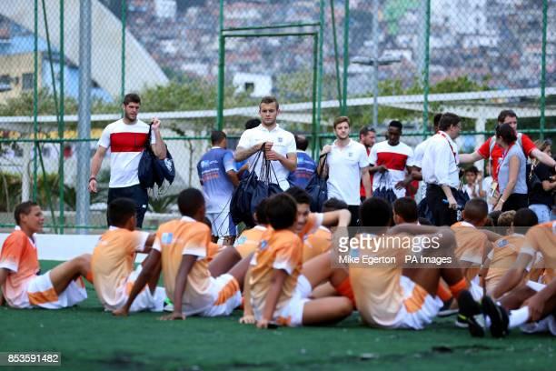 England's Fraser Forster Jack Wilshere Adam Lallana Danny Welbeck and Daniel Sturridge during a visit to the Complexo Esportivo da Rocinha Rio de...