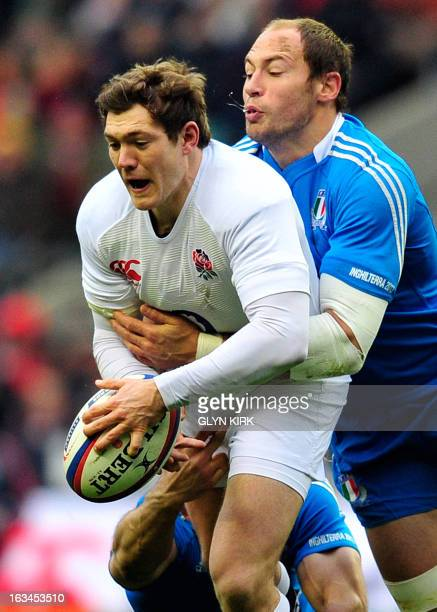 England's full back Alex Goode is tackled by Italy's full back Andrea Masi and Italy's No 8 Sergio Parisse during the Six Nations international rugby...