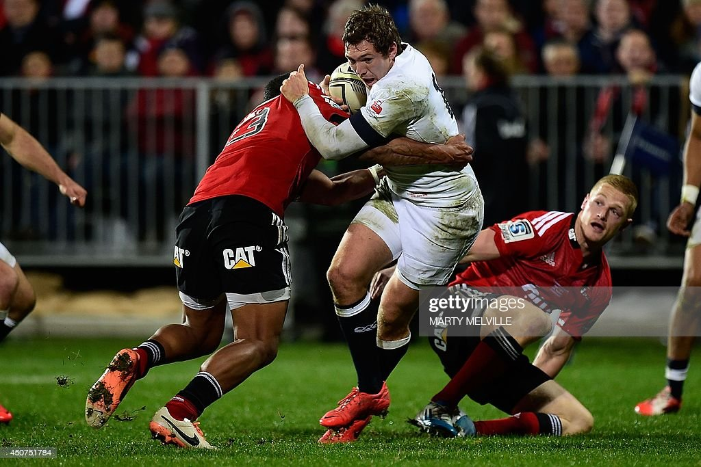 England's fullback Alex Goode (C) is tackled by Canterbury Crusaders outside center Reynold Lee-Lo (L) during their rugby union match at AMI Stadium in Christchurch on June 17, 2014.