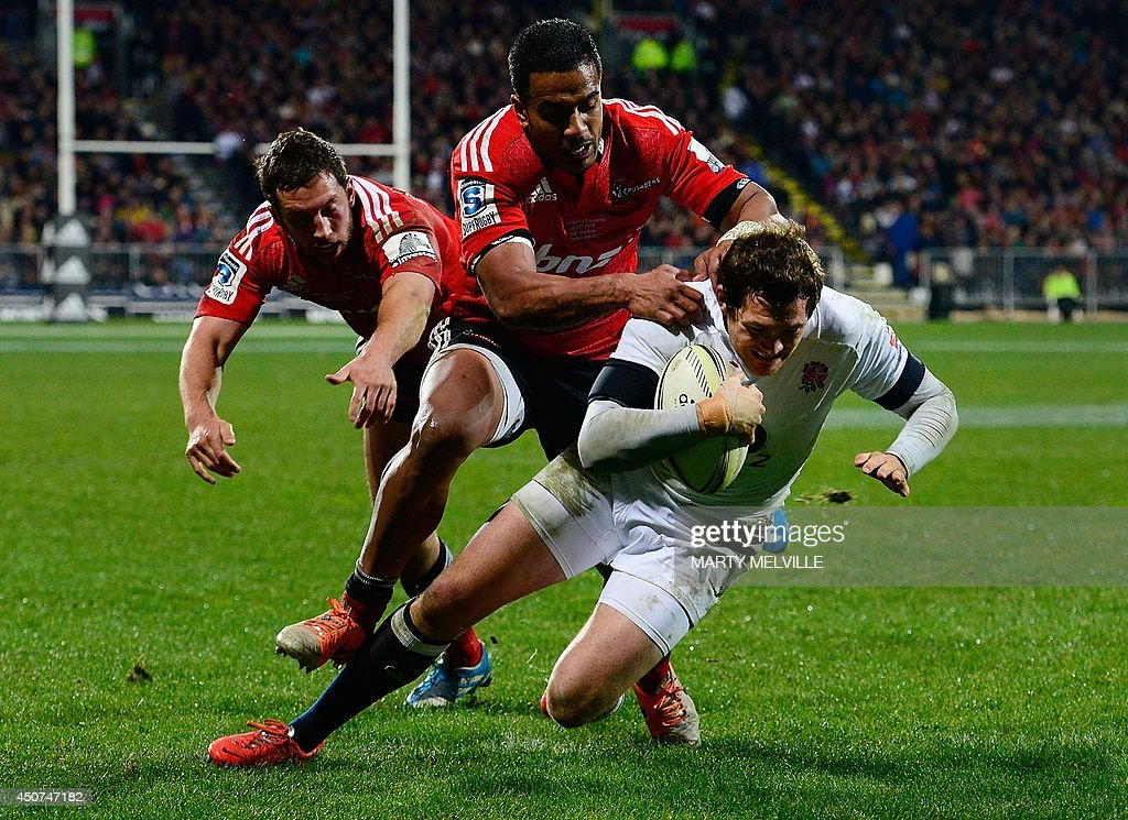 England's fullback Alex Goode (R) scores a try as he is tackled by Canterbury Crusaders outside center Reynold Lee-Lo (C) and fullback Tom Taylor during their rugby union match at AMI Stadium in Christchurch on June 17, 2014.