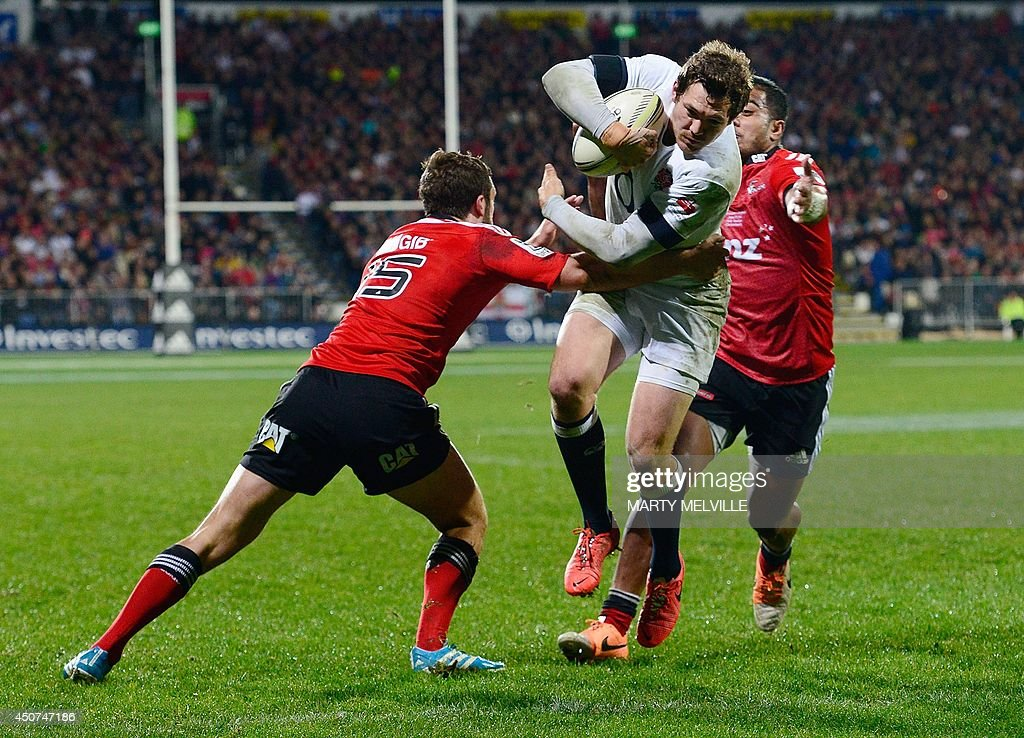 England's fullback Alex Goode (C) scores a try as he is tackled by Canterbury Crusaders outside center Reynold Lee-Lo (R) and fullback Tom Taylor during their rugby union match at AMI Stadium in Christchurch on June 17, 2014. AFP PHOTO / MARTY MELVILLE